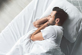 Top view of calm guy napping in his bedroom with enjoyment. Copy space