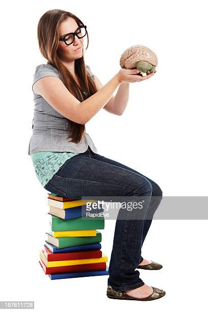 Cute young nerd sits on stack of books contemplating brain