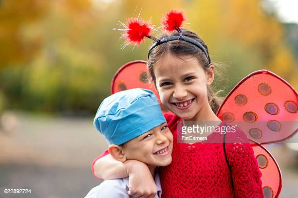 Cute young siblings hugging each other while trick or treating