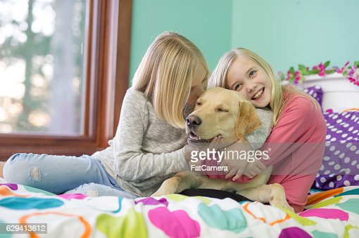 Cute young sisters hugging their yellow labrador on their bed