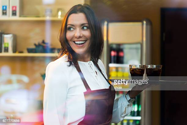 Cute young waitress  in a coffee shopserwing cold drink