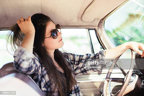 Cute Young Woman Driving Vintage American Car