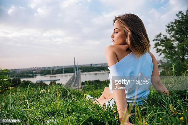 Cute young woman enjoys sunset in summer near Danube river