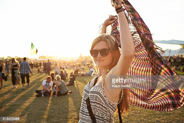 Cute young woman holding up scarf at sunset