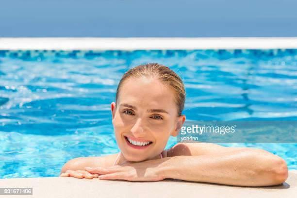 Jolie jeune femme dans la piscine de luxe