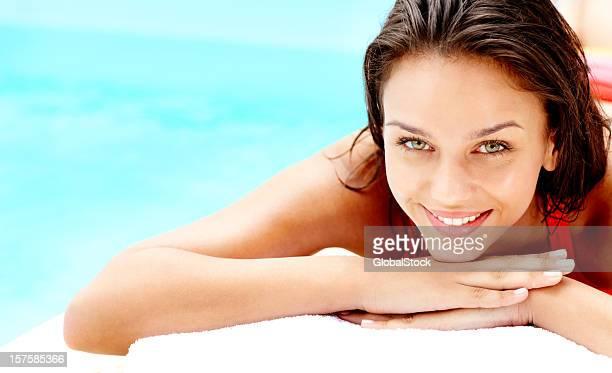 Linda mujer joven estar recostado tranquilo junto a la piscina