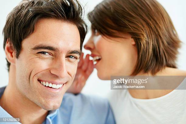 Cute young woman sharing secrets with her husband