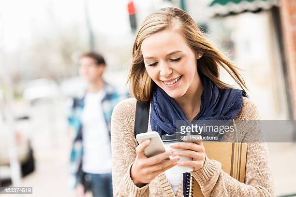 Cute young woman texting on smart phone while walking