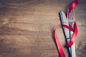 Cutlery Decorated with Red Ribbon on Wooden Background. Selective Focus. Space for Text. Toned image.