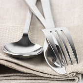 Cutlery set: spoon, fork and knife on linen napkin close-up.