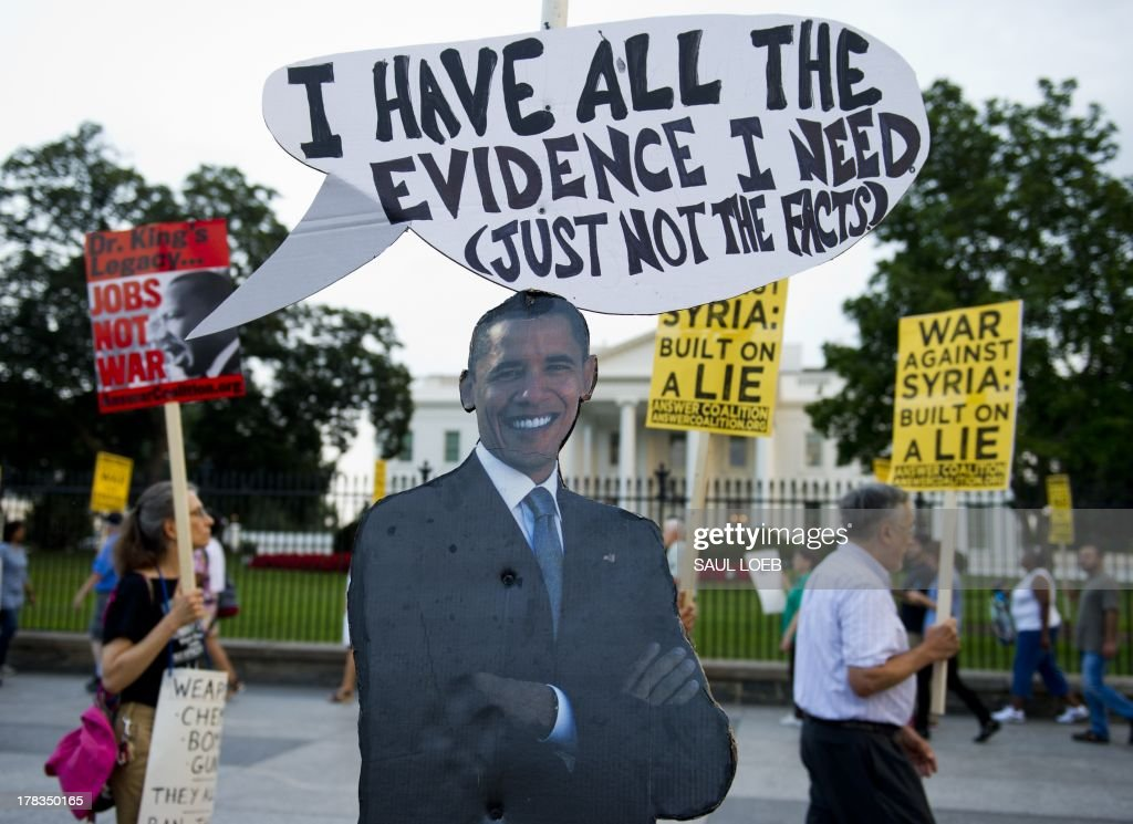 A cutout of US President Barack Obama stands on the sidewalk as demonstrators march in protest during a rally against a possible US and allies attack on Syria in response to possible use of chemical weapons by the Assad government, in Lafayette Park in front of the White House in Washington, DC on August 29, 2013. AFP PHOTO / Saul LOEB