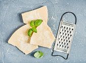 Cuts of Parmesan cheese with metal grater and fresh basil over concrete textured background, top view