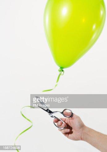 Cutting a balloon loose : Stock Photo