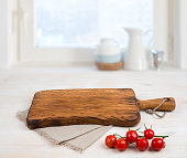 Cutting board above linen tablecloth on wooden table. Cooking concept