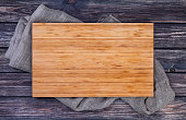 Cutting board on dark wood background, top view