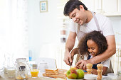 Young father showing his daughter how to cut bread