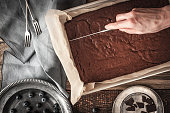 Chocolate brownie on the baking tray  with blueberry , knife in the hand , chocolate , forks and  old vintage plates  on the wooden table horizontal