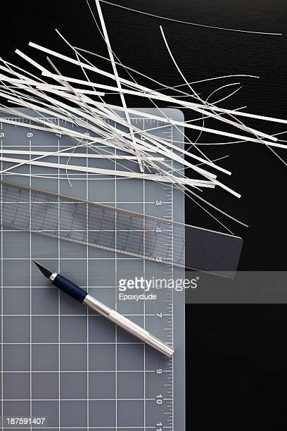 A cutting mat with shredded paper, ruler and utility knife on black background