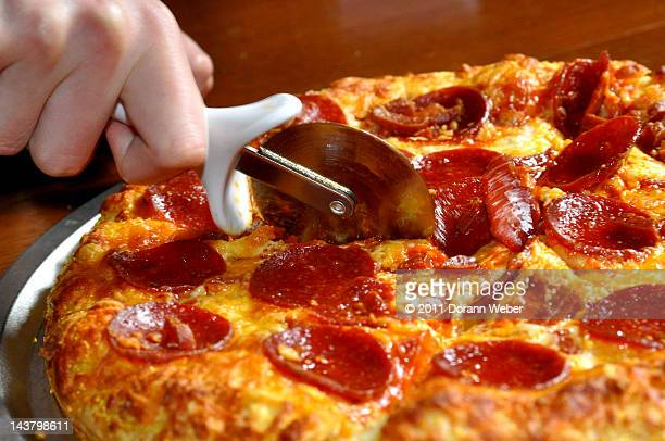 Cutting pepperoni pizza