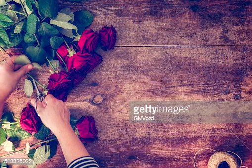 Cutting Romantic Red Roses on Wooden Background