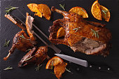 Cutting the roast duck and oranges on a black slate board. horizontal view from above