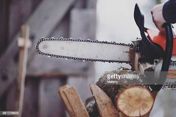Cutting wood with a chainsaw on cold winter day