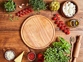 Cutting wooden board with traditional pizza preparation ingridients: mozzarella, tomatoes sauce, basil, olive oil, cheese, spices. Wooden texture table background