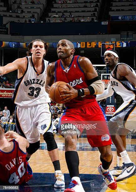 Cuttino Mobley of the Los Angeles Clippers drives past Mike Miller and Hakim Warrick of the Memphis Grizzlies at the FedExForum December 14 2007 in...
