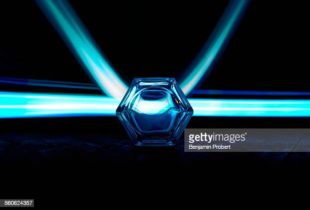 Cyan light streaks through hexagonal glass lens