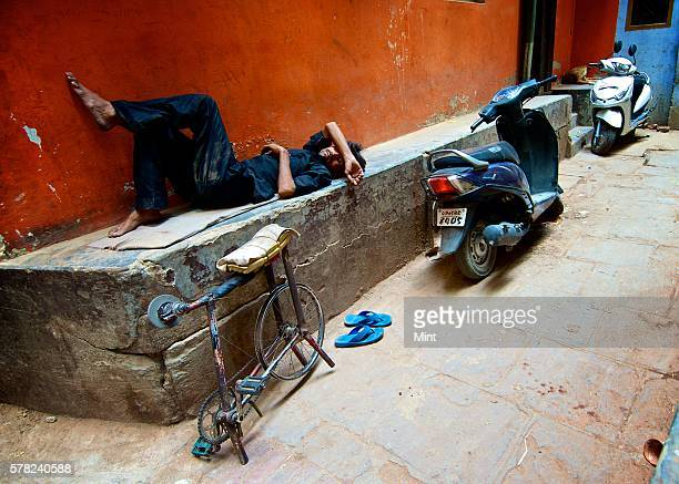 A cycle hawker who sharpens knives taking a break in a lane near Tulsi Ghat on April 26 2016 in Varanasi India Summers in India are not for the...
