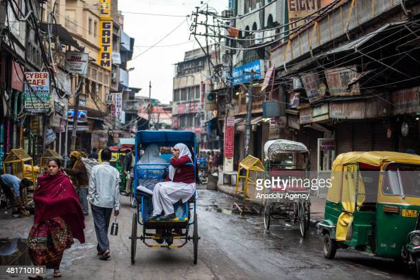 A cycle rickshaw carrying passengers rides in the busy streets of New Delhi's Shahjahanabad the walled old city part of India's capital on March 31...
