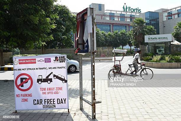 A cycle rickshaw cycles past a no parking notice as Indian traffic police mark areas as no parking zones to promote World Car Free day in Gurgaon...
