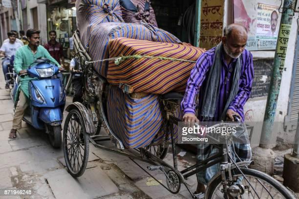 A cycle rickshaw rider transports bundles of clothes along a street in Varanasi Uttar Pradesh India on Saturday Oct 28 2017 In Varanasi where the...