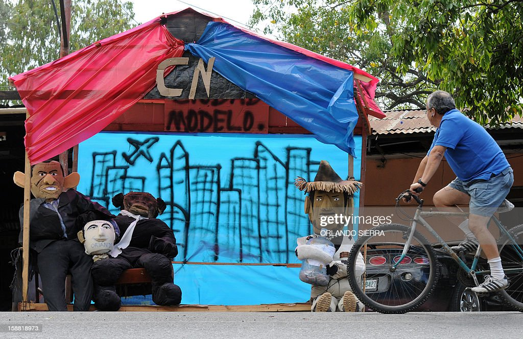 A cycler passes by rag dolls depicting Honduran President Porfirio Lobo, Honduran Congress President Juan Orlando Hernandez, and former Honduran interim de facto President Roberto Micheletti, on December 30, 2012 in Tegucigalpa. Hundurans burn rag dolls to see the 'Old Year' off. AFP PHOTO / Orlando SIERRA