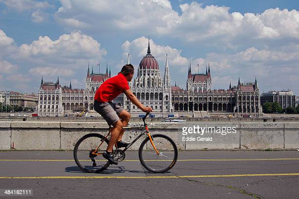 A cycler with view of the Hungarian Parliament Building in Budapest Hungary
