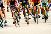 Photo of a cycling competition. Focus on legs