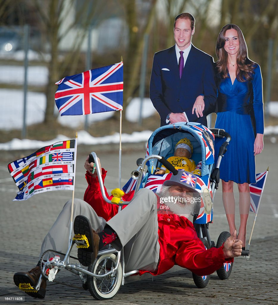 Cycling enthusiast and bicycle designer Dieter (Didi) Senft (front) sits on a self designed bicycle with a children's push chair in front of a stand up display of Britain's prince William and his wife Kate on March 27, 2013 in Storkow, eastern Germany. Senft who is known as a cycling enthusiast has designed more than 200 bicycles so far.