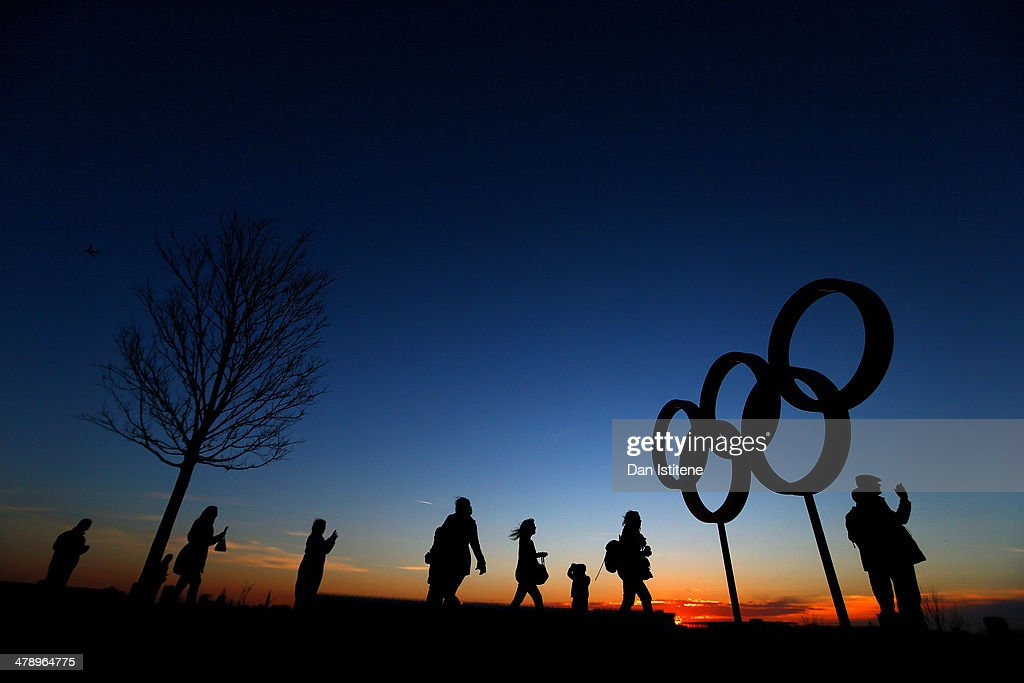 Cycling fans walk past the Olympic Rings at sunset inside the Olympic Park before attending Revolution 5 at the Velodrome in the Lee Valley Velopark on March 15, 2014 in London, England.