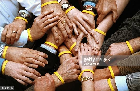 Cycling Generic portrait of Lance Armstrong holding hands with members and advisors wearing LIVESTRONG yellow bands to support foundation Austin TX...