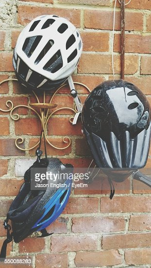 Cycling Helmets Hanging On Brick Wall