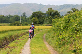 Two people make cycling in a Japanese rural scenery.