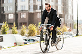 Full length of handsome young businessman looking forward while riding on his bicycle
