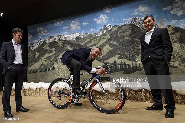 Cycling racers Johan Van Genechten of Belgium and teammate Stefan Denifl of Austria stand between IAM Cyling General Manager Michel Thetaz during the...