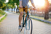 Close up of hipster man riding bicycle hrough the park.