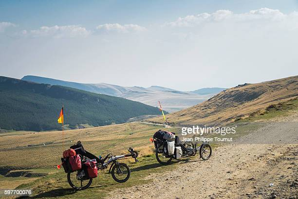 Cycling up a trail in Bucegi Mountains in Romania during a long journey by bicycle