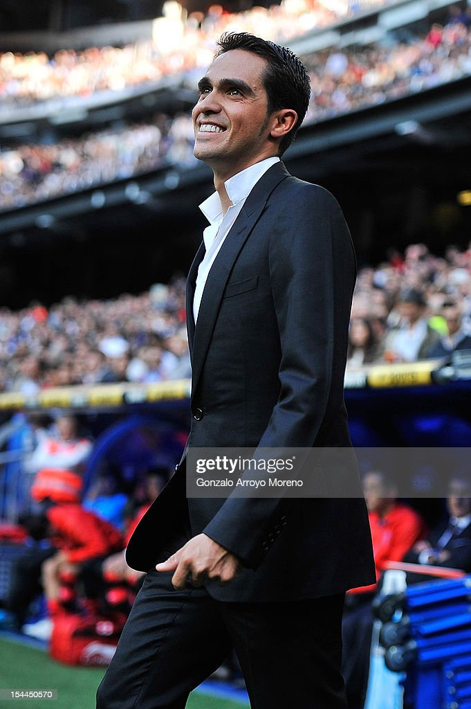 Cyclist <a gi-track='captionPersonalityLinkClicked' href=/galleries/search?phrase=Alberto+Contador&family=editorial&specificpeople=562697 ng-click='$event.stopPropagation()'>Alberto Contador</a> smiles as he walks out onto the pitch kick before the La Liga match between Real Madrid CF and RC Deportivo La Coruna at Bernabeu on October 20, 2012 in Madrid, Spain.