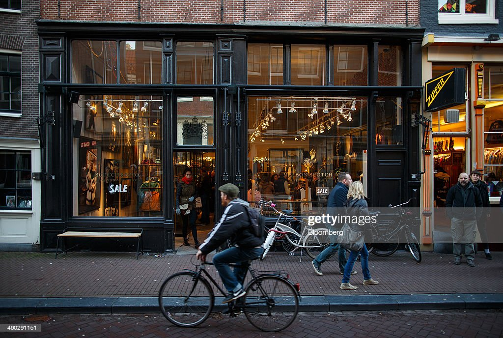 A cyclist and pedestrians pass a women's fashion clothing store in Amsterdam, Netherlands, on Thursday, Jan. 2, 2014. The Netherlands will grow by 0.5 percent in 2014 as the world economy improves and consumer confidence picks up, the country's central bank forecast Dec. 9. Photographer: Jasper Juinen/Bloomberg via Getty Images