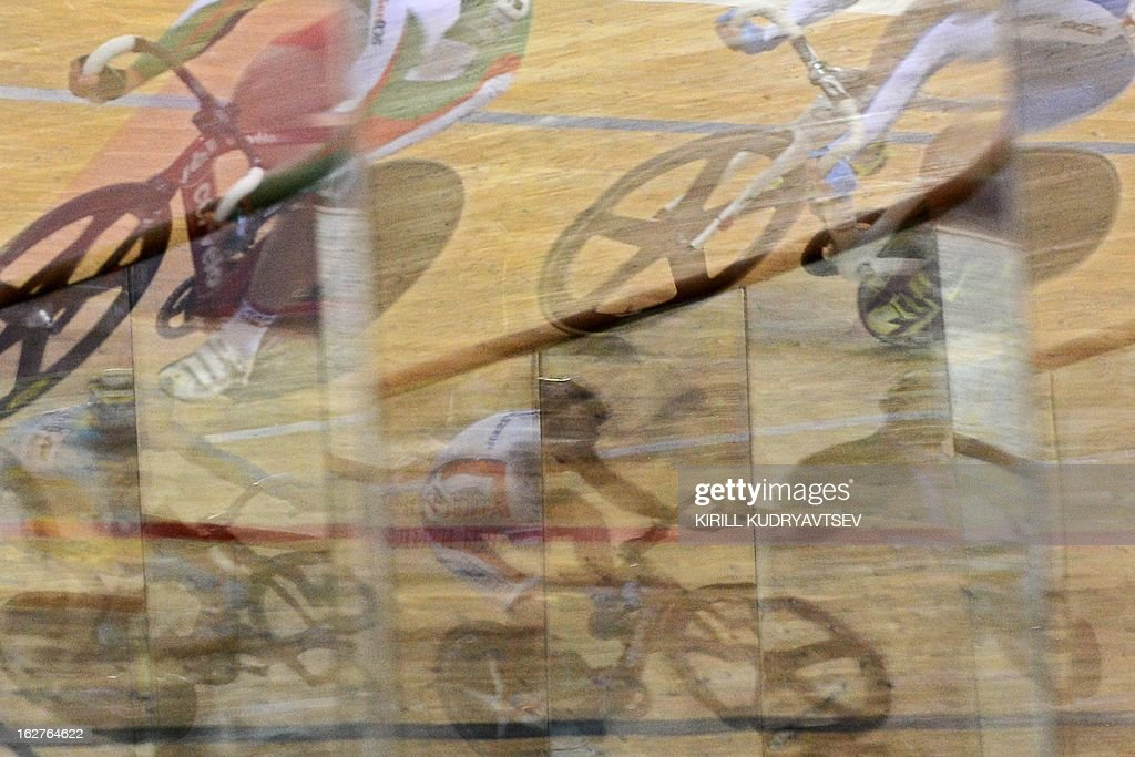 Cyclist are reflected in the track's cover as they compete during UCI Track Cycling World Championships Men's 40 km Point Race in the Belarus capital Minsk on February 22, 2013.