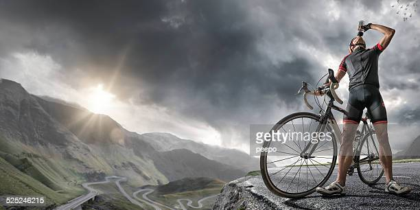 Cyclist At Peak Of Mountain Road