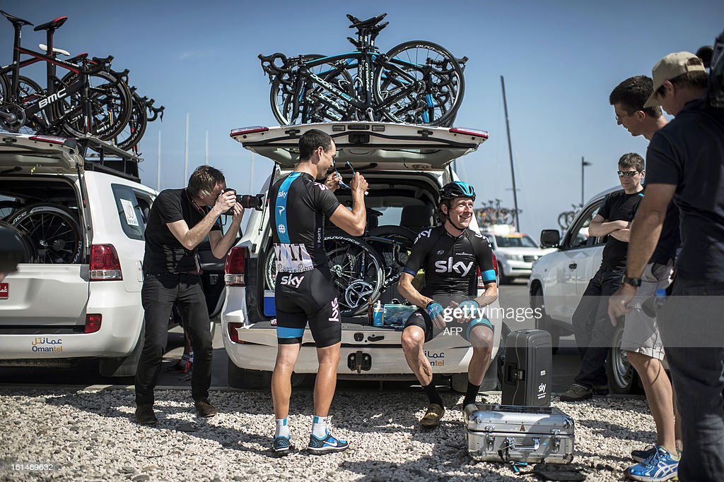 UK cyclist Bradley Wiggins (R sitting) of Sky Pro Cylcling team prepares before the start of the first stage of the Tour of Oman, on February 11, 2013, in Oman. The six-stage race, which follows the Tour of Qatar, won by Britain's Mark Cavendish last week, culminates on Saturday at Matra Corniche. AFP PHOTO/JEFF PACHOUD